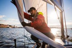 Красивая воодушевляя съемка приключения действия матроса или капитана на яхте или паруснике прикрепляя большой mainsail или стоковое фото rf