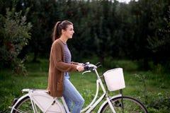 Красивая вскользь девушка с велосипедом на дороге в природе Стоковая Фотография RF