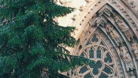 Красивая высокорослая ель рождества в светах против фона старой европейской церков Уточненные figurines на сток-видео