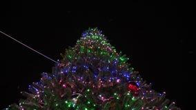 Красивая высокорослая ель рождества украшенная с гирляндами и пестроткаными шариками против ночного неба Меньший снег видеоматериал