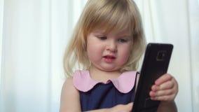 Красивая голубоглазая девушка слегка ударяет через фото на телефоне акции видеоматериалы