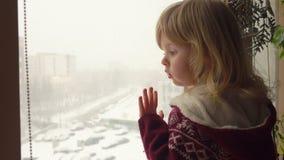 Красивая голубоглазая девушка смотрит через окно акции видеоматериалы