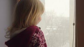 Красивая голубоглазая девушка смотрит через окно сток-видео