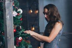 Красивая девушка аранжирует рождественскую елку стоковое фото rf