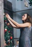 Красивая девушка аранжирует рождественскую елку стоковые изображения
