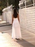 Красивая девушка брюнета в белой стойке платья на улице стоковая фотография