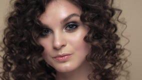 Красивая девушка брюнета с совершенно вьющиеся волосы, и классический макияж представляя в студии Сторона красотки видеоматериал