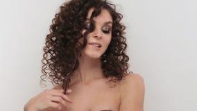 Красивая девушка брюнета с совершенно вьющиеся волосы, и классический макияж представляя в студии Сторона красоты акции видеоматериалы