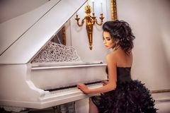Красивая девушка брюнет в дворце сидит на рояле стоковое изображение rf