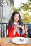 Красивая девушка брюнет в кафе на естественной предпосылке Стоковое Фото