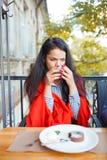 Красивая девушка брюнет в кафе на естественной предпосылке Стоковая Фотография