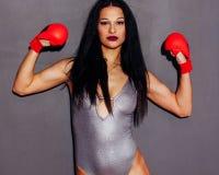 Красивая девушка брюнет в красных перчатках бокса представляя на белой предпосылке Поднятые руки конец вверх крыто Битник стоковое изображение