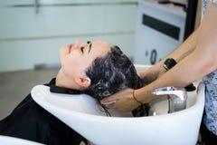 Красивая девушка брюнет моя ее волосы в ` s парикмахера стоковые фото
