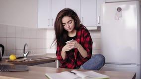 Красивая девушка брюнет отправляя СМС кто-то пока сидящ в кухне ее квартиры акции видеоматериалы