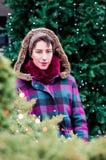 Красивая девушка брюнет перед рождественской елкой outdoors Стоковые Изображения