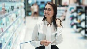 Красивая девушка выбирает косметики в магазине, кладет ее в корзину видеоматериал