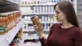 Красивая девушка выбирает продукты питания в магазине сток-видео