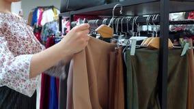 Красивая девушка выбрала брюки в бутике акции видеоматериалы