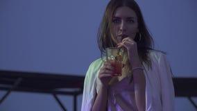 Красивая девушка выпивает коктейль пока сидящ на клубе на летней террасе Коктейль милого сиротливого брюнета выпивая сток-видео