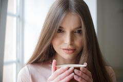 Красивая девушка выпивает кофе и усмехаясь промежуток времени сидя на кафе стоковое изображение rf
