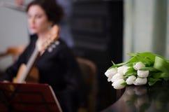 Красивая девушка выполняет игру акустической гитары в черном платье стоковое фото rf