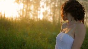 Красивая девушка в белом платье в солнечном лесе лета акции видеоматериалы