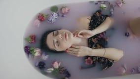 Красивая девушка в ванне молока с душистыми цветками бутонов, касающая кожа фотомодели стороны Концепция заботы курорта и кожи сток-видео