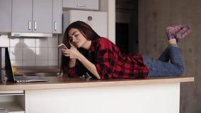 Красивая девушка в ее 20 ` s лежа на ее поверхности кухонного стола отправляя СМС кто-то сток-видео