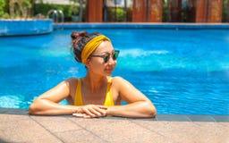 Красивая девушка в желтом купальнике отдыхая в бассейне на гостинице стоковое фото rf