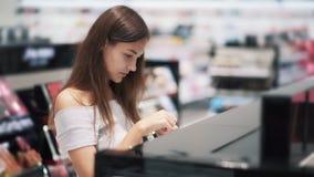 Красивая девушка в косметиках ходит по магазинам выбирает сыворотку стороны, замедленное движение акции видеоматериалы
