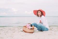 Красивая девушка в красной шляпе с корзиной пикника на портовом районе лета стоковое фото