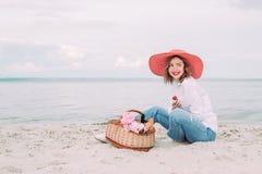 Красивая девушка в красной шляпе с корзиной пикника на портовом районе лета стоковая фотография