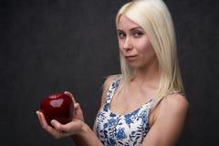 Красивая девушка в модном платье с яблоком стоковая фотография