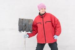 Красивая девушка в одеждах моды зимы с лопаткоулавливателем освобождает дорогу от снега Семья, традиция, праздник Стоковое фото RF