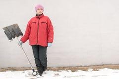 Красивая девушка в одеждах моды зимы с лопаткоулавливателем освобождает дорогу от снега Семья, традиция, праздник Стоковые Изображения RF