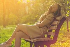 Красивая девушка в парке лета сидя на стенде улицы усмехаться стоковые фотографии rf