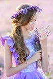 Красивая девушка в поле лаванды на заходе солнца Стоковое Фото