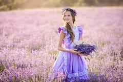 Красивая девушка в поле лаванды на заходе солнца Стоковое Изображение