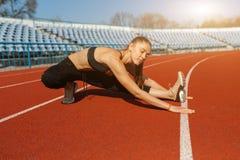 Красивая девушка в положении sportswear на идущем следе и подготовке побежать Подогрев утра перед тренировкой стоковое фото rf