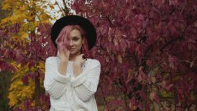 Красивая девушка в представлениях шляпы на дерево пинка осени с улыбкой на стороне сток-видео