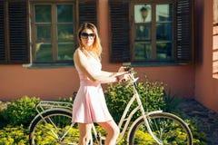 Красивая девушка в розовом платье с цветками на велосипеде стоковые изображения rf