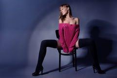 Красивая девушка в связанных свитере и носках сидит на табуретке внутри стоковое фото rf
