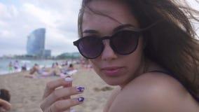 Красивая девушка в солнечных очках сидя на пляже Женщина с развевая волосами на ветре акции видеоматериалы