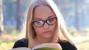 Красивая девушка в стеклах читая книгу в лесе сток-видео
