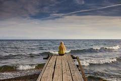 Красивая девушка в стиле моря сидя на деревянном мосте Перемещение и каникула черная изолированная свобода принципиальной схемы Ч стоковое изображение rf