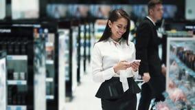 Красивая девушка в торговой площадке использует телефон, смотрит мобильный экран видеоматериал