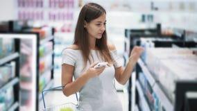 Красивая девушка в торгуя пользах магазина знонит по телефону и выбирает косметикам, замедленному движению сток-видео