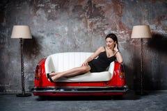 Красивая девушка в черном платье сидит на необыкновенной handmade софе Софа от автокресла Стоковые Фотографии RF