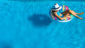 Красивая девушка в шляпе во взгляде сверху бассейна воздушном сверху, женщина ослабляет и плавает на раздувном донуте кольца и им стоковые фотографии rf