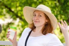 Красивая девушка в шляпе держит стекло кофе и представлять против зеленой предпосылки Стоковые Изображения RF